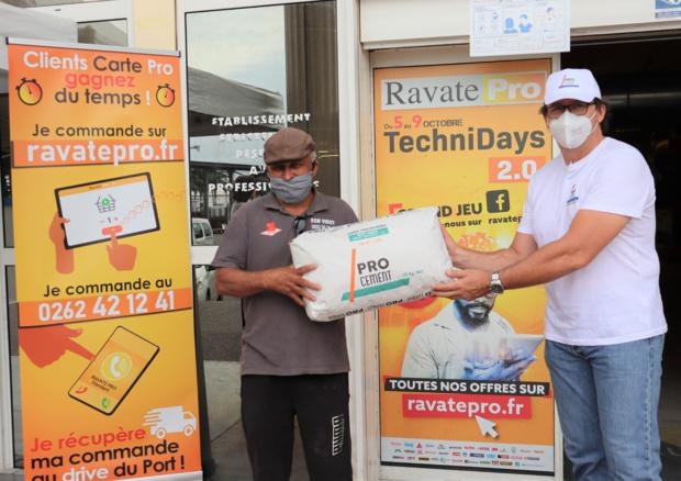 Christophe Commins, représentant de Pro Cement, qui remet un sac de ciment à Joseph Vidot, un artisan convaincu par le produit