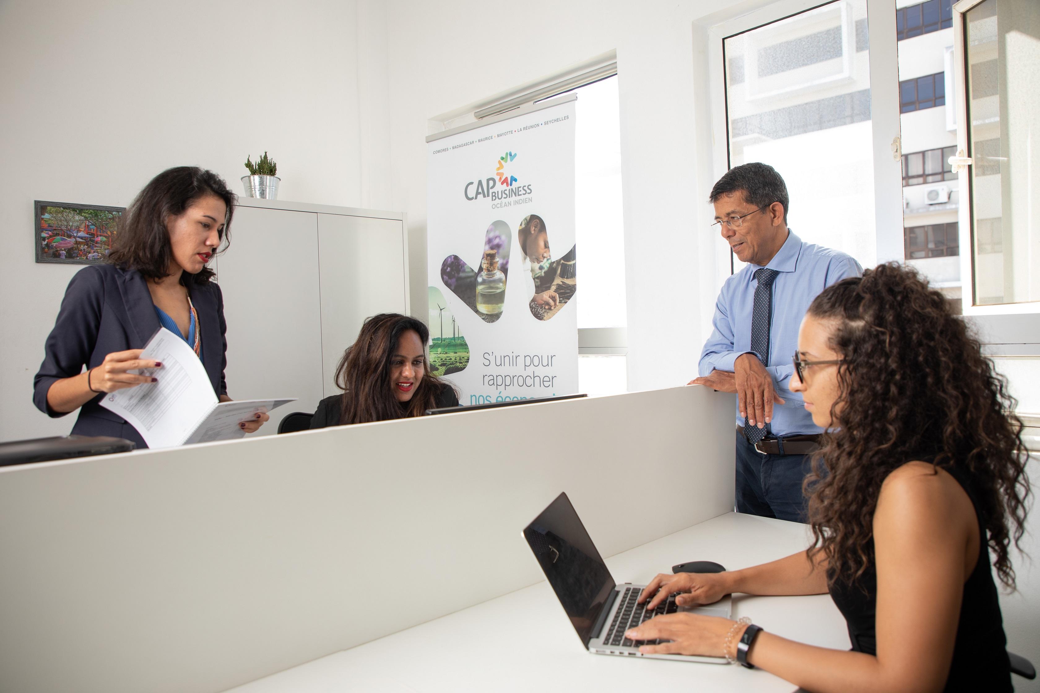 Éric Magamootoo, Secrétaire général de Cap Business Océan Indien en séance de briefing avec son équipe. De gauche à droite : Virginie Lauret, Directrice de Programme, Samantha, Comptable/Administrateur, et Johanna Domitile, Chargée de missions Filières régionales.